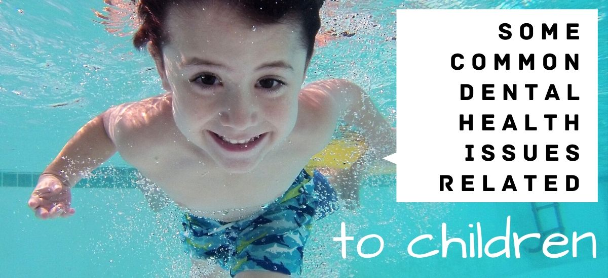 Young boy smiling underwater in a pool